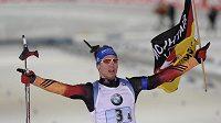 Německý biatlonista Simon Schempp slaví s vlajkou vítězství ve štafetě.