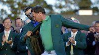 Obhájce titulu Jordan Spieth (vlevo) pomáhá letošnímu vítězi golfového Masters Dannymu Willetovi obléct zelené sako.