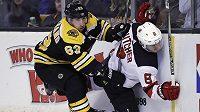 Hokejista Bostonu Bruins Brad Marchand (63) napadá obránce New Jersey Devils Willa Butchera (8).