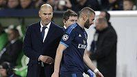 Fotbalista Realu Madrid Karim Benzema vedle kouče Zinedina Zidana opouští hřiště na szadiónu Wolfsburgu po zranění.