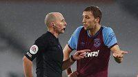 Český fotbalista ve službách West Hamu Tomáš Souček (vpravo) diskutuje s rozhodčím po vyloučení v zápase s Fulhamem.