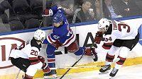 Český obránce NY Rangers Libor Hájek (v modrém) mezi Blakeam Colemanem (20) a Ericem Tangradim (34) během třetí třetiny utkání NHL mezi NY Rangers a New Jersey.