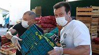 Carlos Dunga (vpravo) a Andres D'Alessandro pomáhají s distribucí potravin.