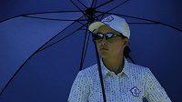 Min Lee z Tchajwanu se schovává před sluníčkem. Deštník bude možná potřebovat také v sobotu, kdy se očekávají bouřky, uvažuje se také o zkrácení soutěže na 3 kola