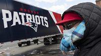 Žena s ochranou obliečeje sleduje náklaďák týmu New England Patriots.