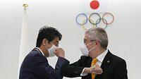 Bývalý japonský premiér Šinzó Abe a Thomas Bach, šéf MOV, během setkání v Tokiu.