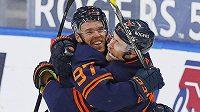 Hokejista Edmontonu Oilers Connor McDavid oslavuje svůj 100. bod v sezoně s útočníkem Leonem Draisaitlem.