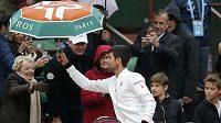 Novak Djokovič si půjčuje deštník od fanynky.