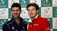 Srbský tenista Novak Djokovič (vlevo) a Španěl Pablo Carreno Busta před daviscupovým duelem