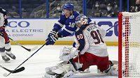 Náhradní brankář Columbusu Blue Jackets Elvis Merzlikins likviduje šance útočníka Tampy Bay Lightning Ondřeje Paláta během utkání NHL.