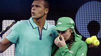 Francouzský tenista Jo-Wilfried Tsonga pomáhá otřesené sběračce