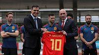 Šéf španělského svazu Luis Rubiales (vpravo) předává dres národního týmu novému předsedovi vlády Pedru Sanchezovi.