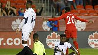 Kanadský útočník Jonathan David (20) slaví gól. Zklamaní Kubánci Erick Rizo (3) a brankář Sandy Sanchez (1) sedí na zemi během utkání Ligy národů CONCACAF.