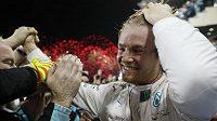 Nico Rosberg slaví s ohňostrojem za zády triumf v posledním závodě sezóny.