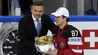 Prezident Mezinárodní hokejové federace René Fasel (vlevo) předává pohár pro mistry světa kapitánovi Kanady Sidneymu Crosbymu.