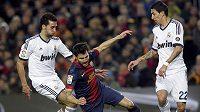 Barcelonský Cesc Fabregas (uprostřed) padá mezi dvojící hráčů Realu Madrid Alvarem Arbeolou (vlevo) a Angelem di Mariou.