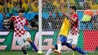 Brazilský útočník Fred (ve žlutém dresu) padá k zemi po souboji s chorvatským stoperem Dejanem Lovrenem (vpravo). Japonský sudí Nišimura nařídil pokutový kop pro domácí Kanárky.