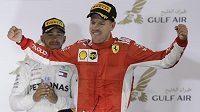 Sebastian Vettel z Ferrari slaví triumf ve Velké ceně Bahrajnu. Za ním stojí úřadující světový šampión Lewis Hamilton.