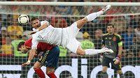 Olivier Giroud, nová posila londýnského Arsenalu, v akrobatické pozici při souboji se Španělem Gerardem Piguém v utkání francouzské reprezentace na ME