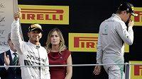 Lewis Hamilton (vlevo) zdraví diváky po vítězství v Monze. Nico Rosberg radost svého týmového parťáka nesdílel.