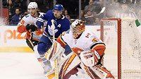 Auston Matthews z Toronta se v utkání NHL proti Calgary tlačí před českého brankáře Davida Ritticha.
