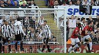 Fotbalisté Newcastlu United (v bíločerných dresech) smutní po gólu Jonnyho Evanse z Manchesteru United.
