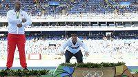 Němec Christoph Harting se chystá vyskočit na stupně po bok dalšího medailisty Piotra Malachowského z Polska.