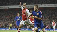 Jack Wilshere z Arsenalu (vlevo) a Luke Shaw z Manchesteru United bojují o míč.