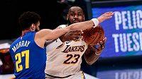 Hvězdný LeBron James z Los Angeles Lakers se snaží projít přes bránícího Jamala Murrayho z Denveru.