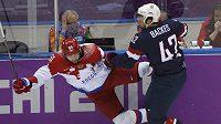 Ruský hokejista Fjodor Tjutin (vlevo) padá na led po souboji s Američanem Davidem Backesem.