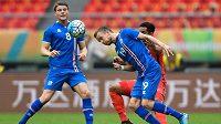 Islandský reprezentant Sigurdur Egill Larusson (číslo 19) hlavičkuje během utkání na China Cupu proti Chile.