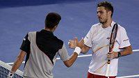 Novak Djokovič (zády) gratuluje svému přemožiteli Stanislasu Wawrinkovi.