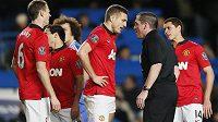 Obránce Manchesteru United Nemanja Vidič (uprostřed) diskutuje s rozhodčím Philem Dowdem.
