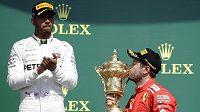 Sebastian Vettel z Ferrari se laská s trofejí pro vítěze Velké ceny Británie. Vlevo nahoře mu tleská jeho největší rival Lewis Hamilton z Mercedesu.