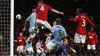 Zadák Manchesteru United Phil Jones (4) namířil svou hlavičku do zad Vincenta Kompanyho z Manchesteru City, od kterého se míč odrazil za brankovou čáru.