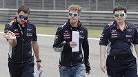 Pilot Red Bullu Sebastian Vettel (uprostřed) si spolu se členy týmu prochází trať Velké ceny Číny v Šanghaji.