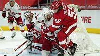 Brankář Caroliny Petr Mrázek sleduje počínání Tylera Bertuzziho z Detroitu v utkání NHL.