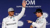 Lewis Hamilton (vlevo) zdraví diváky po triumfu v kvalifikaci na GP Brazílie. Nico Rosberg (vpravo) skončil druhý.