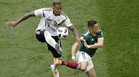 Německý obránce Jerome Boateng odehrává míč před Javierem Hernándezem z Mexika.