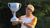 Golfista Rickie Fowler si prohlíží trofej pro vítěze turnaje v Bostonu.