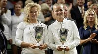 Barbora Krejčíková (vpravo) s Kateřinou Siniakovou pózují s trofejemi pro vítězky ženské čtyřhry na Wimbledonu.