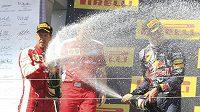 Sebastian Vettel (vlevo) v Maďarsku získal první triumf v barvách Ferrari a oslavy na pódiu si jaksepatří užil.
