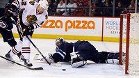 Český forvard Tomáš Fleischmann (12) z Chicaga překonává svého krajana v bráně Winnipegu Ondřeje Pavelce (30) v zápase NHL.