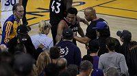 Kyle Lowry (uprostřed) gestikuluje k rozhodčímu Marcu Davisovi. Fanoušek sedící u postranní čáry byl vyveden poté, co do Lowryho strčil, když hráč spadl mezi diváky.