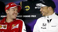 Pilot Ferrari Sebastian Vettel (vlevo) žertuje na tiskové konferenci před GP Číny s Jensonem Buttonem z McLarenu.