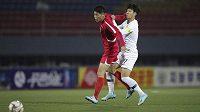 Jihokorejec Son Hung-min (vpravo) bojije o míč s Ri Yong Cholem z KLDR.