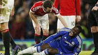 Zraněný obránce Chelsea Kurt Zouma se svíjí v bolestech v duelu s Manchesterm United.