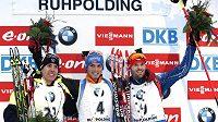 Vítěz nedělního závodu s hromadným startem, biatlonista Simon Schempp z Německa, vlevo druhý Francouz Quentin Fillon-Maillet a třetí Michal Šlesingr.