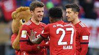 Fotbalisté Bayernu Mnichov Thomas Müller a David Alaba slaví po vítězství v bundesligovém utkání.