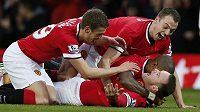 Fotbalisté Manchesteru United slaví gól proti Liverpoolu, jehož autorem byl Wayne Rooney (dole).